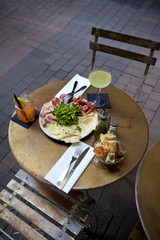 Ham, cheese and green salad on a plate, drinks in a French bistr