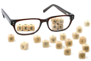 "glasses and message ""see more"" written in wooden blocks, isolate"