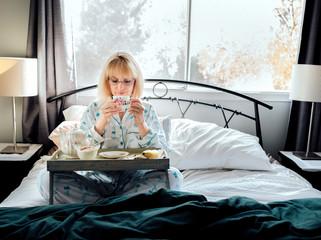 Mature Woman Having Breakfast in Bed