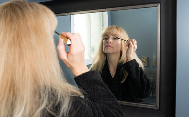 Mature Woman Applying Eyeliner in the Morning