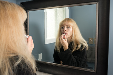Mature Woman Applying Lipstick in the Morning