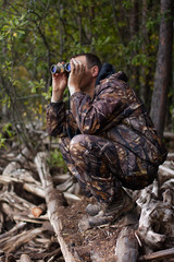 man with binoculars out hunting