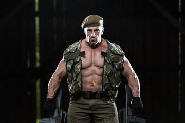 Muscular Man Holding Machine Guns