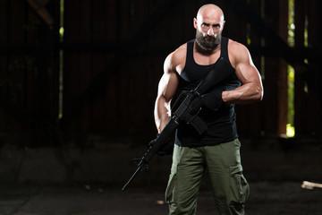 Muscular Man Holding Machine Gun