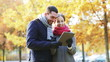 smiling couple with tablet pc in autumn park