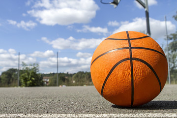 Basketball  on an outdoor court on a sunny day