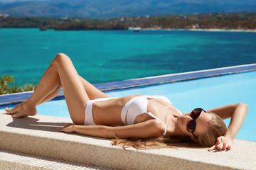Young beautiful woman sunbathing. Nice sea view.