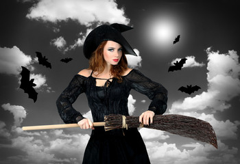 Halloween witch with broom on grey sky background