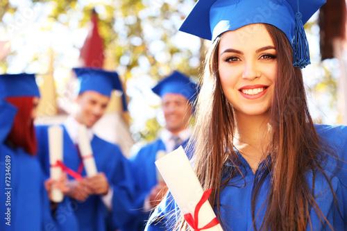 Leinwanddruck Bild Graduate students wearing graduation hat and gown, outdoors