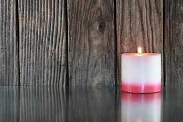 Kerze vor Holzstruktur