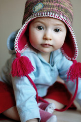 A little girl in a warm funny cap