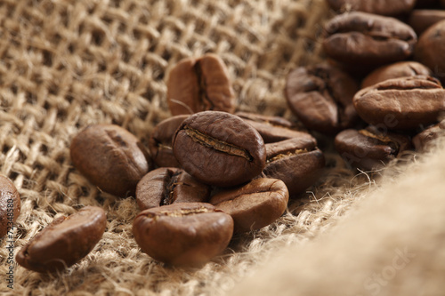 Closeup of coffee beans on a sack cloth. © sumire8