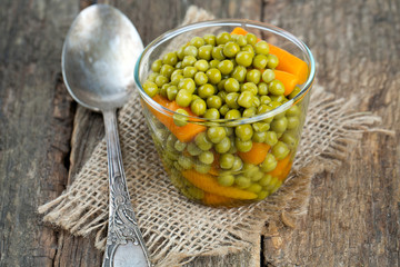 canned peas and carrots on wooden surface