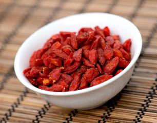 Dehydrated goji berries in bowl on oriental mat