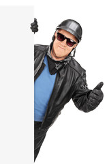 Mature biker giving thumb up behind a panel