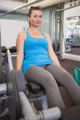 Fit brunette using weights machine for legs