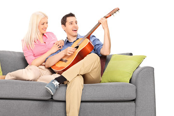 Young guy playing guitar with his girlfriend
