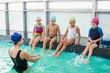 Cute swimming class watching the coach - 72350953