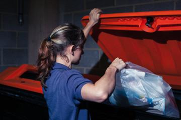 Woman putting rubbish in bin