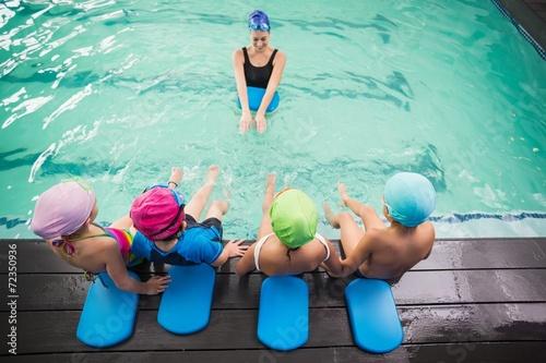 Cute swimming class watching the coach - 72350936