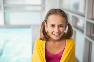 Cute little girl sitting poolside