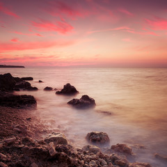 Seashore with misty water at sunset