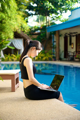 Girl sitting with laptop at pool