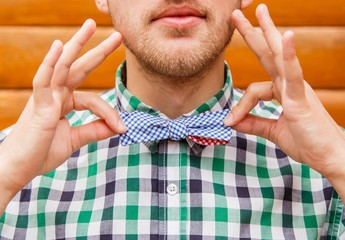 Young man in casual shirt correcting his retro bowtie
