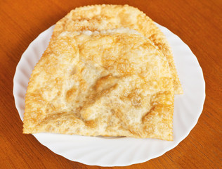 top view of chiburekki pie on white plate