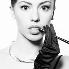 Audrey Hepburn style concept. Fashionable model smoking