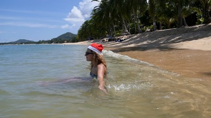 Happy Young Woman on the Beach in the Sea in Santa Hat.