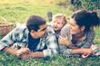 Leinwanddruck Bild - Happy family of three lying in the grass in autumn