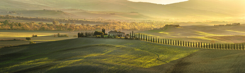 Panoramic view of Tuscan house with cypress trees along the road