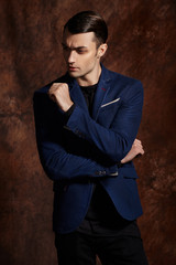 Fashion young man blue suit on brown background