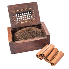 Dried, processed tea leaves in wooden box with cinnamon stick