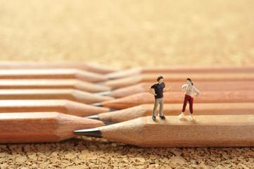 鉛筆の上に座って語り合っているミニチュアの人形