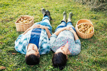 Couple resting on the grass in autumn after picking apples
