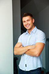 Portrait of a happy handsome man with arms folded