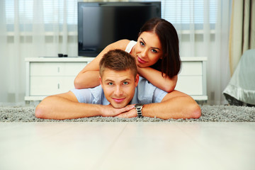 Smiling couple lying on the floor at home