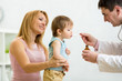 Doctor giving spoon dose of medicine drinking syrup to child