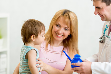 doctor counseling mother and boy about nasal irrigation