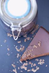 piece of chocolate cake with large jar of chocolate