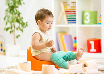 smiling baby sitting on chamber pot with toilet paper