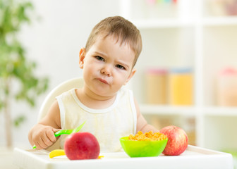 displeased kid boy with healthy food at kitchen