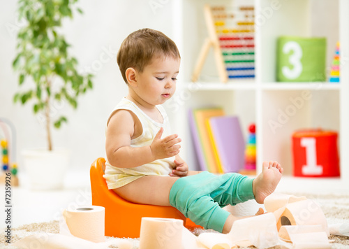 smiling baby sitting on chamber pot with toilet paper - 72359926