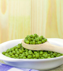 A wooden spoonful of fresh green peas with copy space background