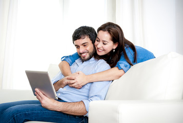 couple on couch using digital tablet computer online internet