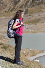 Young woman hiking in nature watching lake landscape