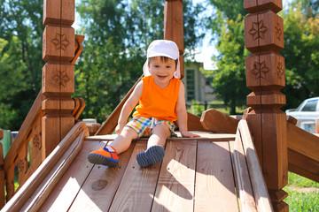 little child sliding on playground in summer