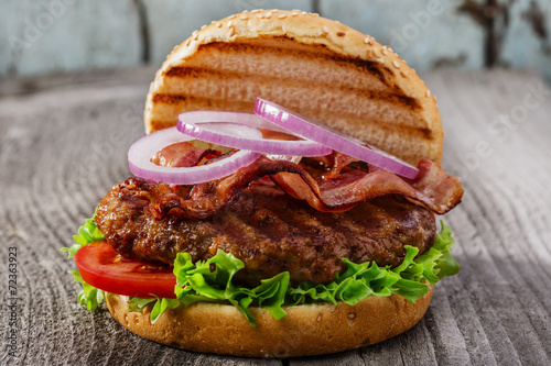 hamburger with bacon and grilled meat on a wooden surface